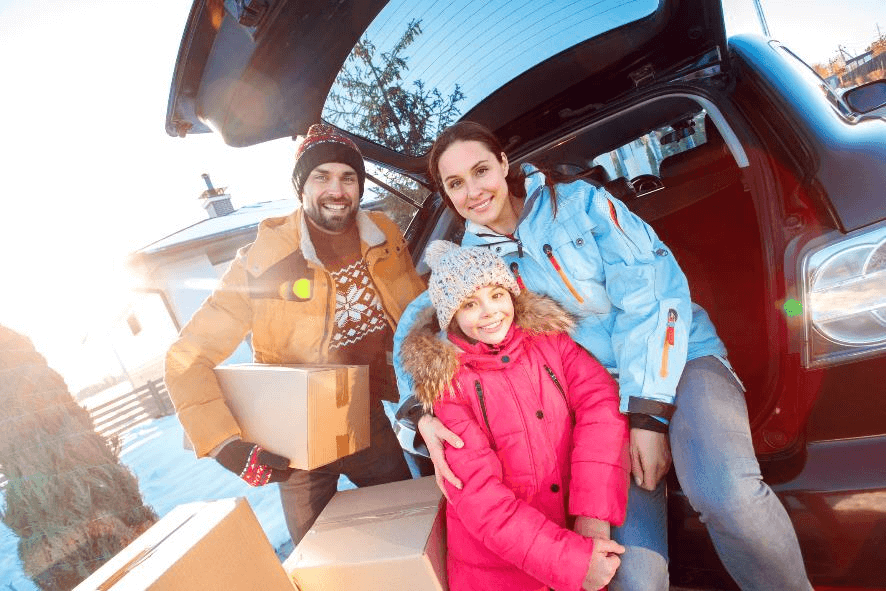 family smiling during winter with moving boxes